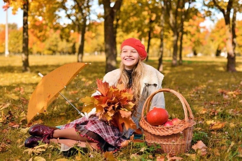 ευτυχής χαμογελώντας έφ&e Πορτρέτο φθινοπώρου του όμορφου νέου κοριτσιού στο κόκκινο καπέλο στοκ εικόνα με δικαίωμα ελεύθερης χρήσης