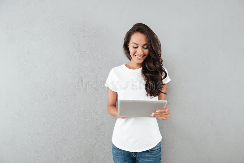 Ευτυχής χαμογελώντας ασιατική γυναίκα που χρησιμοποιεί τον υπολογιστή ταμπλετών στοκ εικόνες
