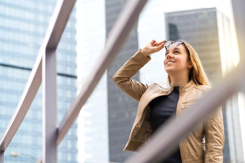 Ευτυχής χαμογελώντας γυναίκα στη μεγάλη πόλη με τους ουρανοξύστες στοκ φωτογραφία με δικαίωμα ελεύθερης χρήσης