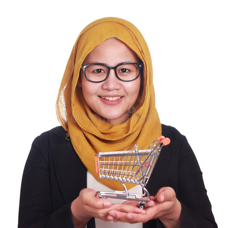 Ευτυχής χαμογελώντας επιτυχής ασιατική μουσουλμανική γυναίκα που παρουσιάζει μίνι καροτσάκι αγορών σε ετοιμότητα της στοκ εικόνες
