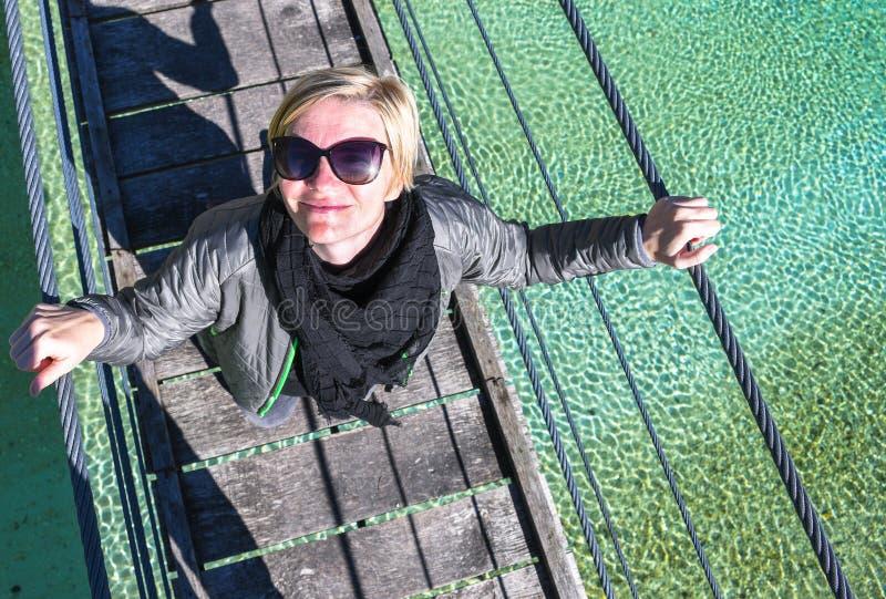 Ευτυχής χαμογελώντας και χαλαρώνοντας γυναίκα σε ένα ταξίδι ημέρας που στέκεται σε μια παλαιά ξύλινη κρεμώντας γέφυρα στοκ φωτογραφία με δικαίωμα ελεύθερης χρήσης