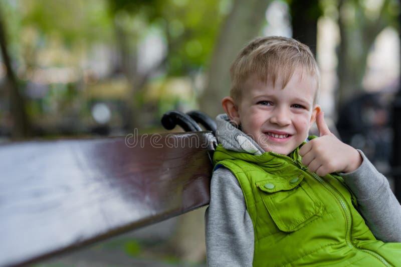 Ευτυχής χαμογελώντας λίγο ξανθό αγόρι παρουσιάστε εντάξει συνεδρίαση σημαδιών σε έναν πάγκο, στοκ εικόνα