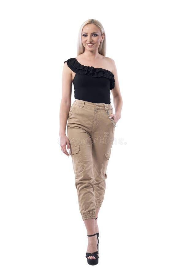 Ευτυχής χαμογελώντας νέα ελκυστική ξανθή γυναίκα στα μοντέρνα ενδύματα που περπατά προς τη κάμερα στοκ φωτογραφία