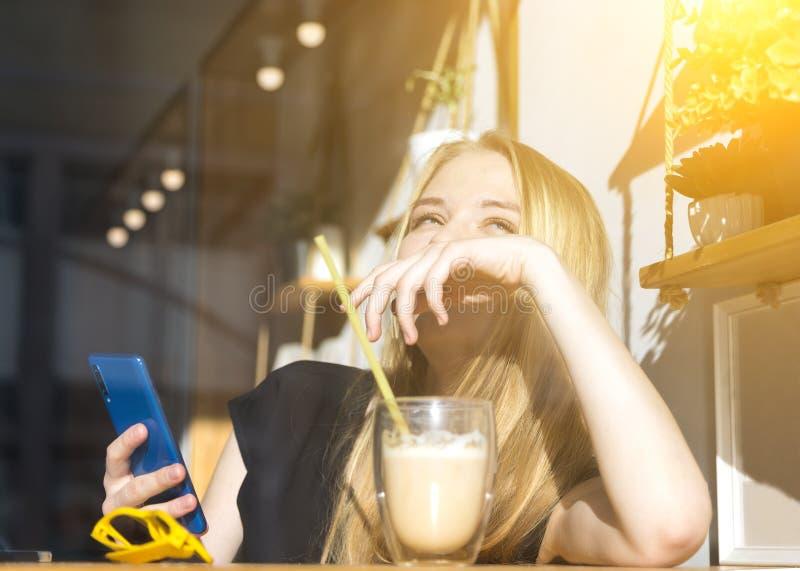 ευτυχής χαμογελώντας νέα ξανθή γυναίκα που πίνει ένα latte σε έναν καφέ για ένα γυαλί, τα γυαλιά ηλίου και το τηλέφωνο στο πρώτο  στοκ φωτογραφία με δικαίωμα ελεύθερης χρήσης