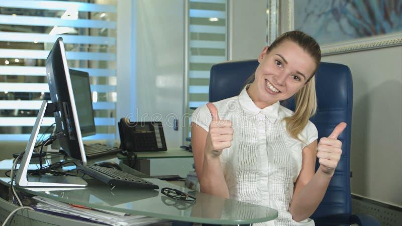 Ευτυχής χαμογελώντας όμορφη νέα επιχειρηματίας που παρουσιάζει εντάξει συνεδρίαση χειρονομίας στην αρχή στοκ εικόνα