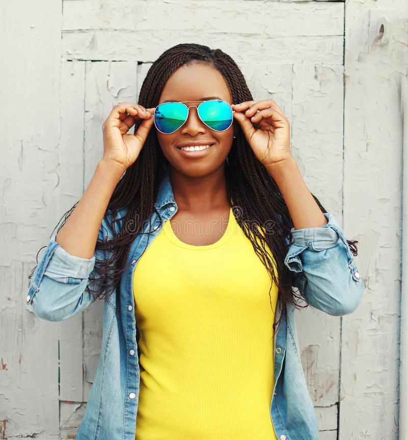 Ευτυχής χαμογελώντας αφρικανική γυναίκα στα ζωηρόχρωμα ενδύματα και τα γυαλιά ηλίου στοκ εικόνες με δικαίωμα ελεύθερης χρήσης