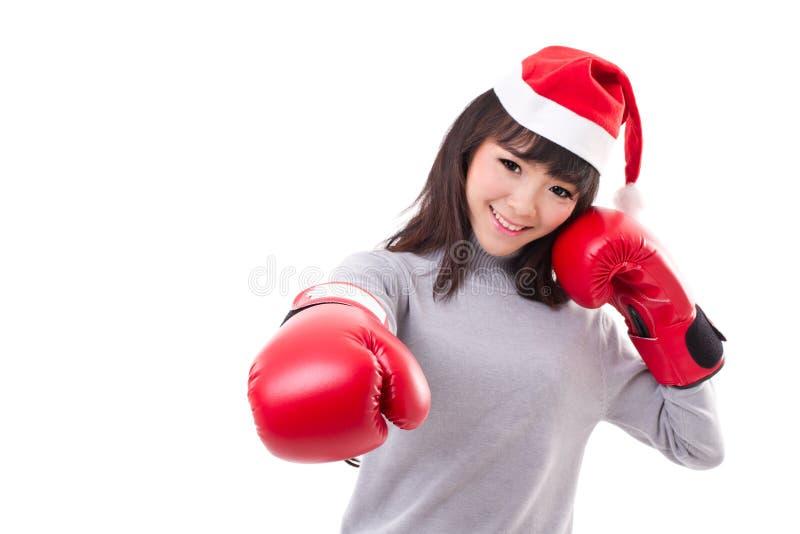 Ευτυχής, χαμογελώντας γυναίκα που φορά το καπέλο santa Χριστουγέννων, εγκιβωτίζοντας γάντια στοκ εικόνες