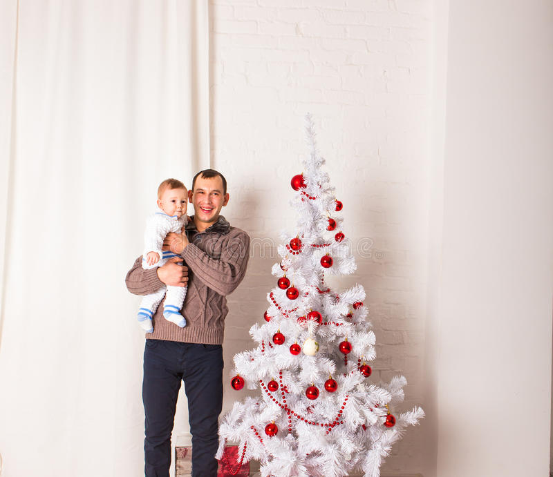 Ευτυχής χαμογελώντας πατέρας με το αγοράκι κοντά στα Χριστούγεννα στοκ φωτογραφίες