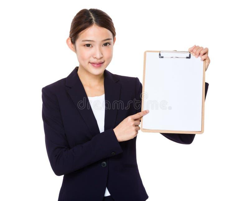Ευτυχής χαμογελώντας όμορφη νέα επιχειρησιακή γυναίκα που παρουσιάζει κενό clipb στοκ εικόνα