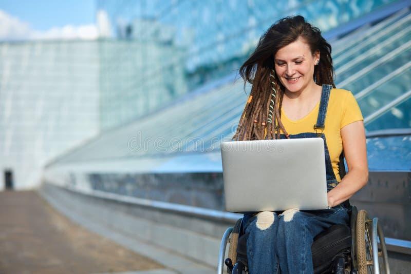 Ευτυχής χαριτωμένη επιχειρηματίας στην αναπηρική καρέκλα που λειτουργεί χρησιμοποιώντας ένα lap-top στοκ εικόνες
