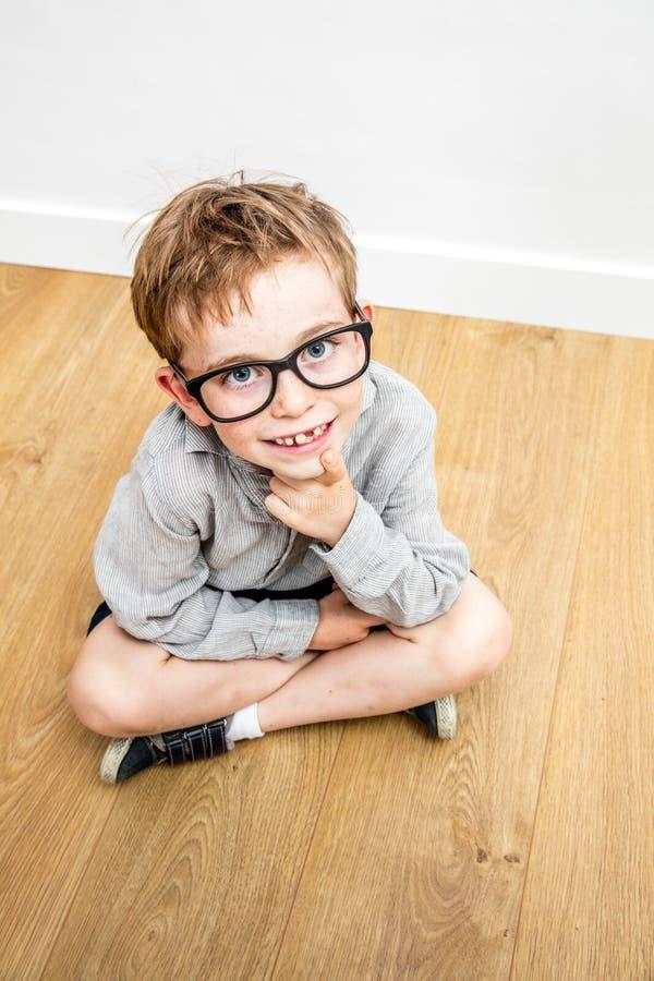 Ευτυχής χαριτωμένος μαθητής σοβαρά eyeglasses και να λείψει δοντιών που κάθεται με στοκ φωτογραφίες