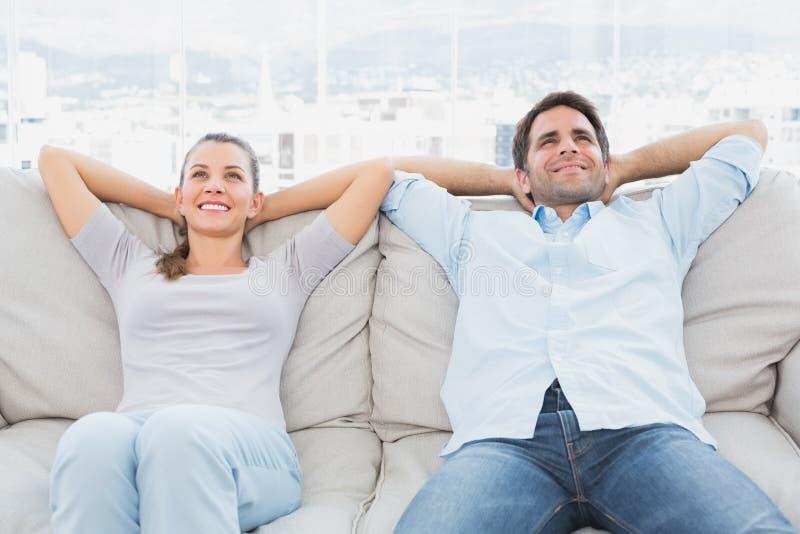Ευτυχής χαλάρωση ζευγών στον καναπέ στοκ εικόνες