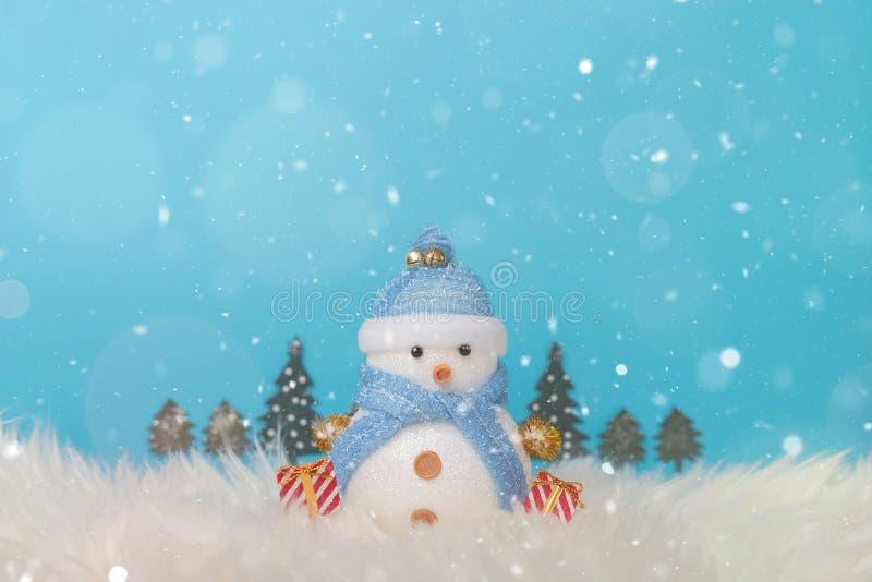 Ευτυχής χιονάνθρωπος που στέκεται στο μπλε υπόβαθρο χιονιού χειμερινών Χριστουγέννων Τοπίο Χριστουγέννων με τα δώρα και το χιόνι  στοκ φωτογραφία