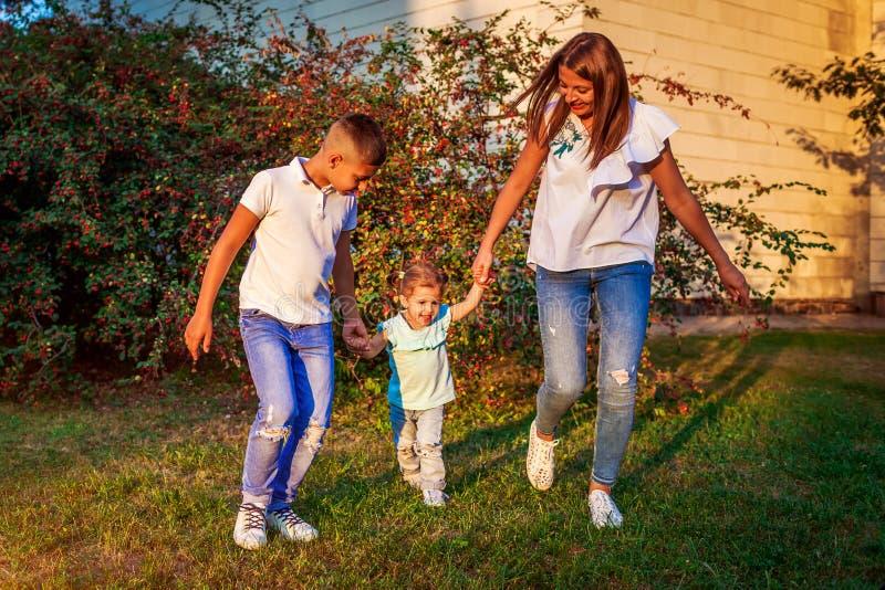Ευτυχής χρόνος οικογενειακών εξόδων που περπατά υπαίθρια στο πάρκο Μητέρα και ο γιος της που κρατούν λίγο κορίτσι μικρών παιδιών  στοκ φωτογραφίες με δικαίωμα ελεύθερης χρήσης