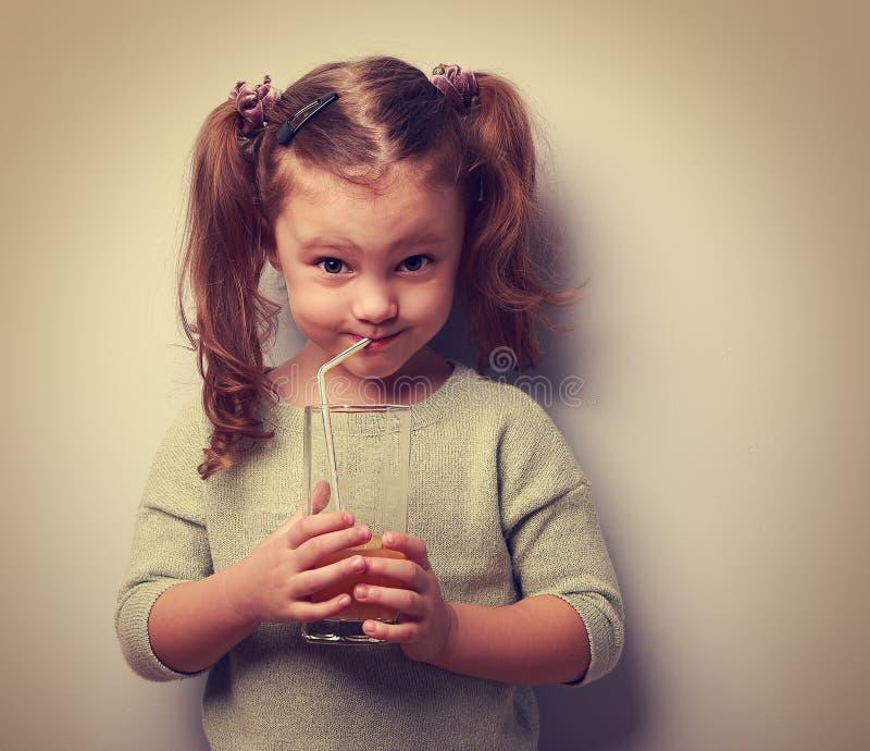 Ευτυχής χυμός κατανάλωσης παιδιών από το γυαλί και να φανεί χιούμορ στοκ εικόνες με δικαίωμα ελεύθερης χρήσης
