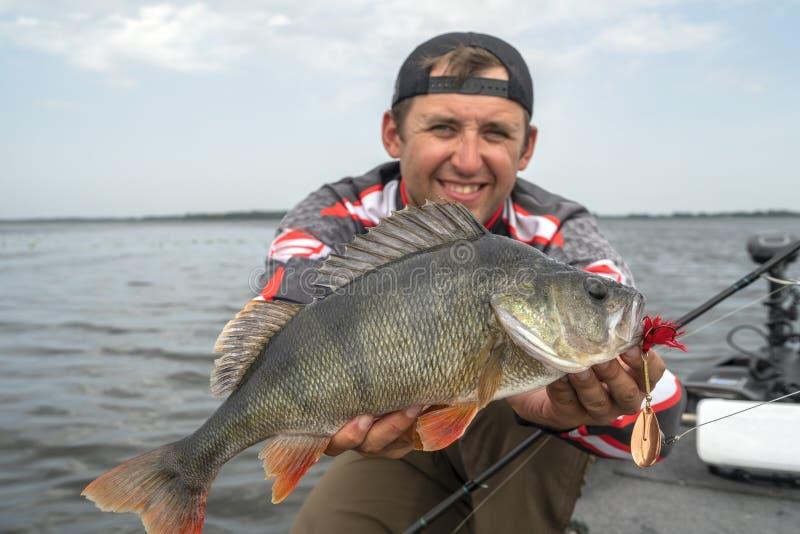 Ευτυχής ψαράς με το μεγάλο τρόπαιο ψαριών περκών στη βάρκα στοκ εικόνα