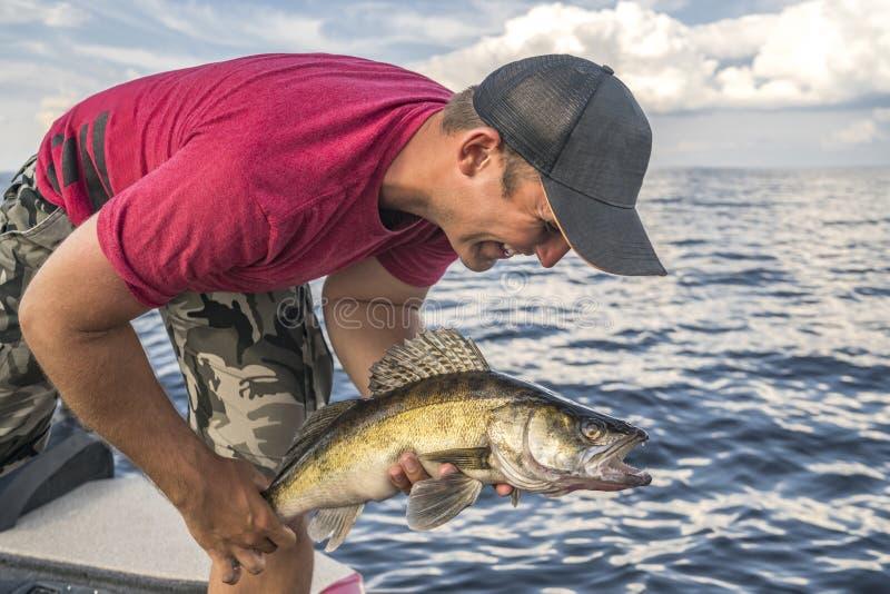 Ευτυχής ψαράς με walleye zander το τρόπαιο ψαριών στη βάρκα στοκ εικόνες με δικαίωμα ελεύθερης χρήσης