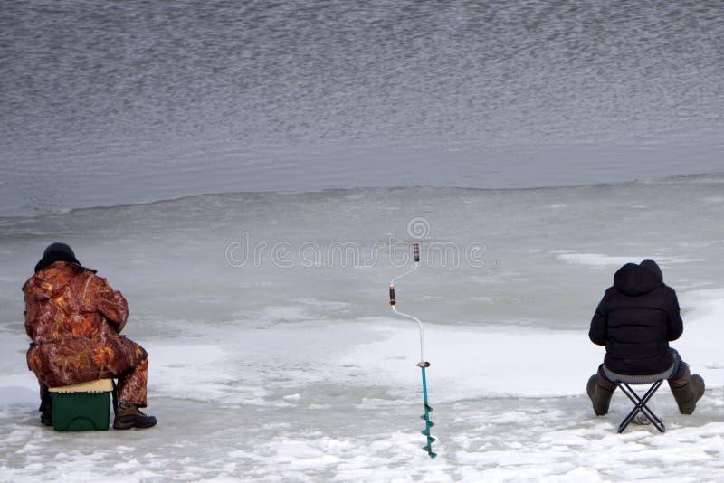 Ευτυχής ψαράς που παλεύει ένα ψάρι αλιεύοντας πάγου στοκ εικόνες