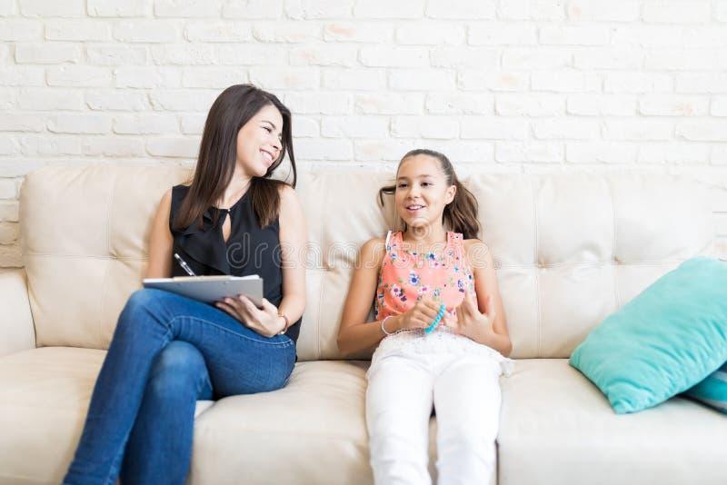 Ευτυχής ψυχολόγος που εξετάζει το κορίτσι κάνοντας τις σημειώσεις στοκ φωτογραφία με δικαίωμα ελεύθερης χρήσης