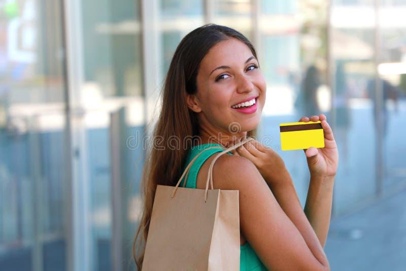 Ευτυχής ψωνίζοντας γυναίκα που παρουσιάζει πιστωτική κάρτα της Κορίτσι με την τσάντα αγοραστών που κρατά την πιστωτική κάρτα της  στοκ εικόνα