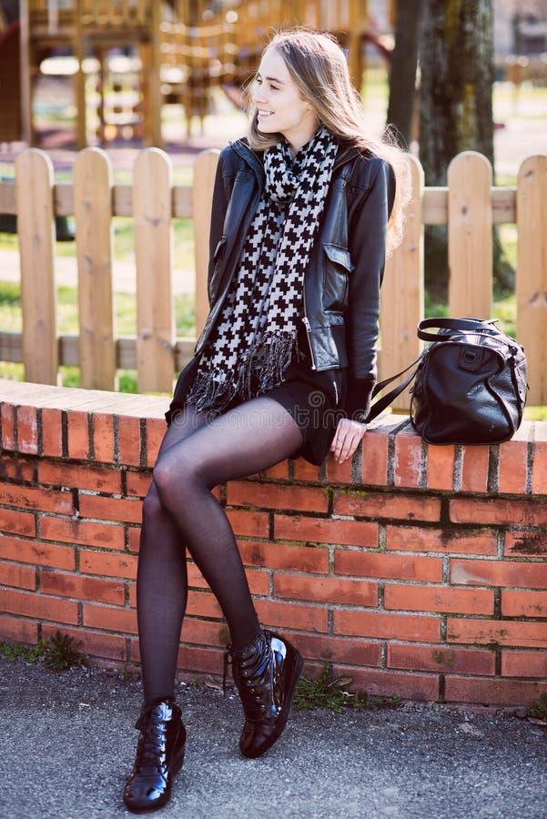 όμορφη γυναίκα με τα μακριά πόδια που κάθεται στο πάρκο στοκ εικόνες