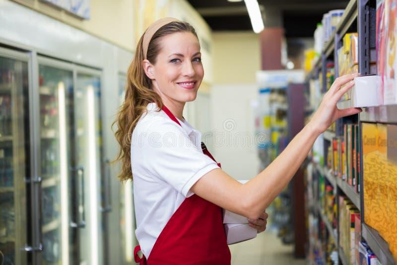 Ευτυχής όμορφη γυναίκα που βάζει το προϊόν στο ράφι στοκ φωτογραφίες με δικαίωμα ελεύθερης χρήσης