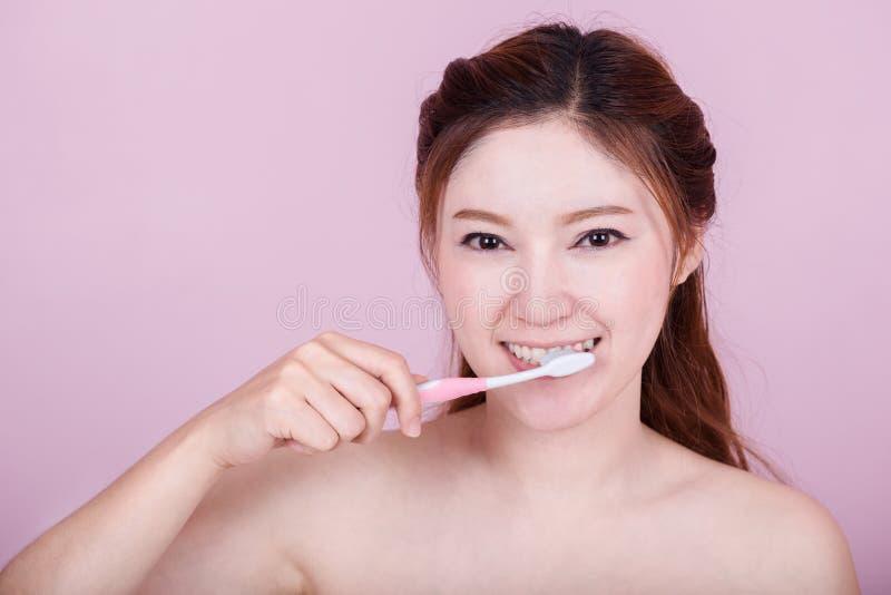 Ευτυχής όμορφη γυναίκα που βουρτσίζει τα δόντια της στοκ εικόνα με δικαίωμα ελεύθερης χρήσης