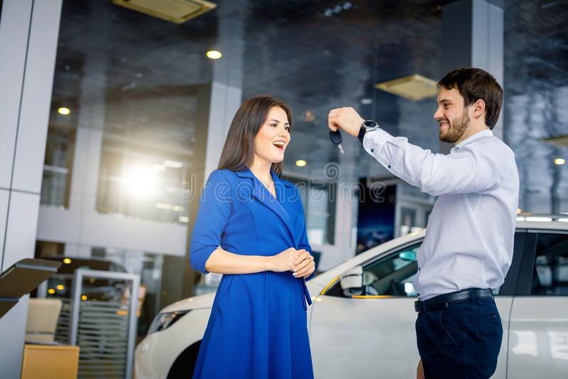 Ευτυχής όμορφη γυναίκα που λαμβάνει τα κλειδιά από ένα νέο αυτοκίνητο στην αυτόματη αίθουσα εκθέσεως στοκ εικόνες