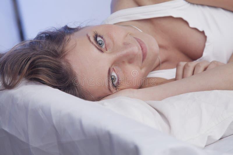 Ευτυχής όμορφη γυναίκα που ξυπνά και πλήρως στηριγμένος στο κρεβάτι της στοκ φωτογραφίες με δικαίωμα ελεύθερης χρήσης