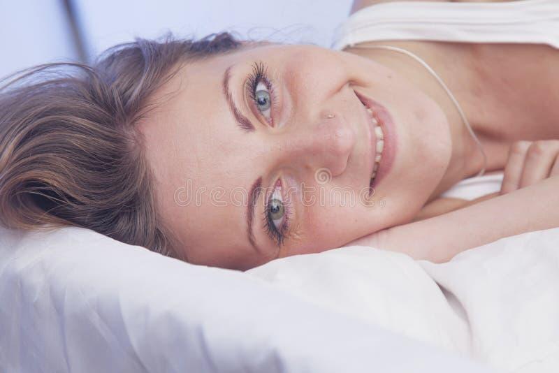 Ευτυχής όμορφη γυναίκα που ξυπνά και πλήρως στηριγμένος στο κρεβάτι της στοκ εικόνες