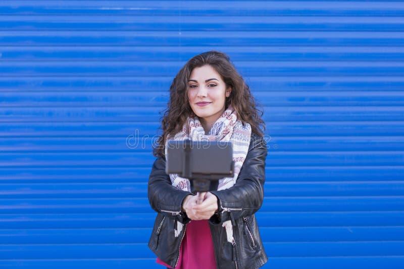 Ευτυχής όμορφη γυναίκα που παίρνει ένα selfie με το έξυπνο τηλέφωνο πέρα από το μπλε στοκ φωτογραφία