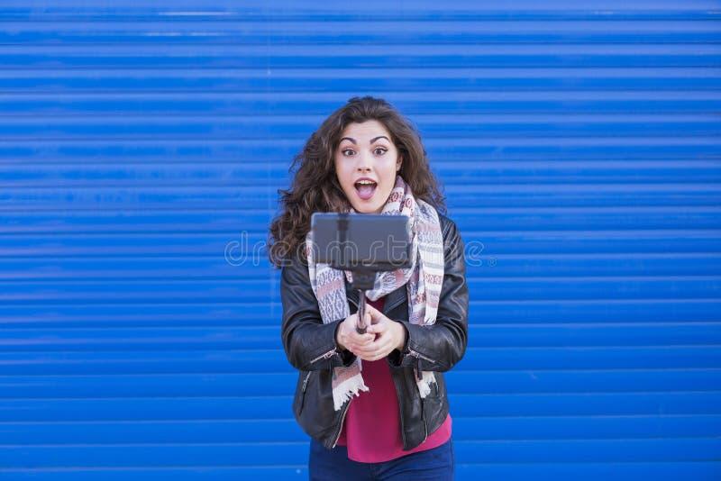 Ευτυχής όμορφη γυναίκα που παίρνει ένα selfie με το έξυπνο τηλέφωνο πέρα από το μπλε στοκ φωτογραφίες