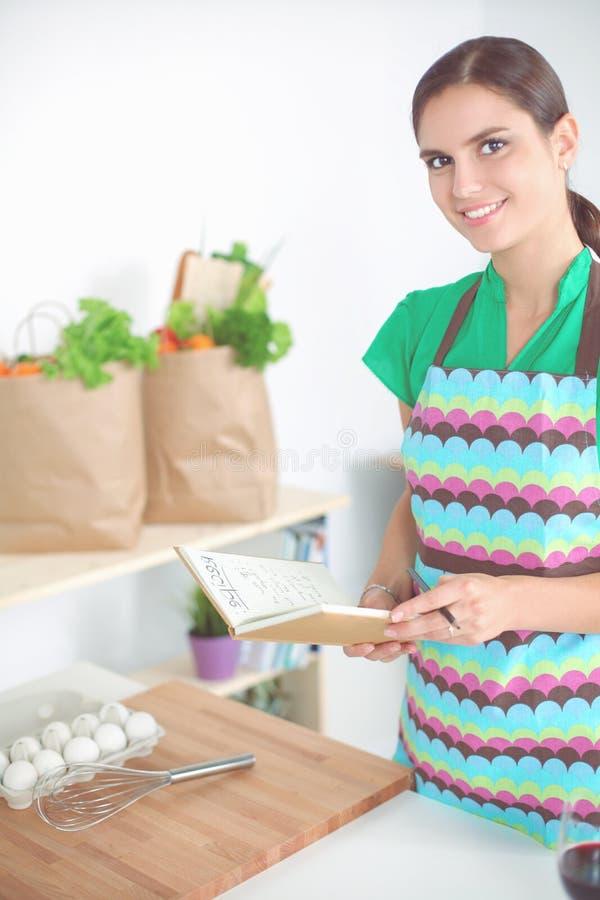 Ευτυχής όμορφη γυναίκα που στέκεται στην κουζίνα της που γράφει σε ένα σημειωματάριο στο σπίτι στοκ φωτογραφίες