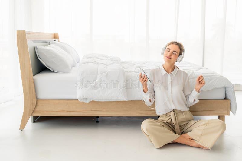 Ευτυχής όμορφη γυναίκα στα ακουστικά που ακούνε τη μουσική και που τραγουδούν καθμένος στο κρεβάτι στοκ εικόνα με δικαίωμα ελεύθερης χρήσης