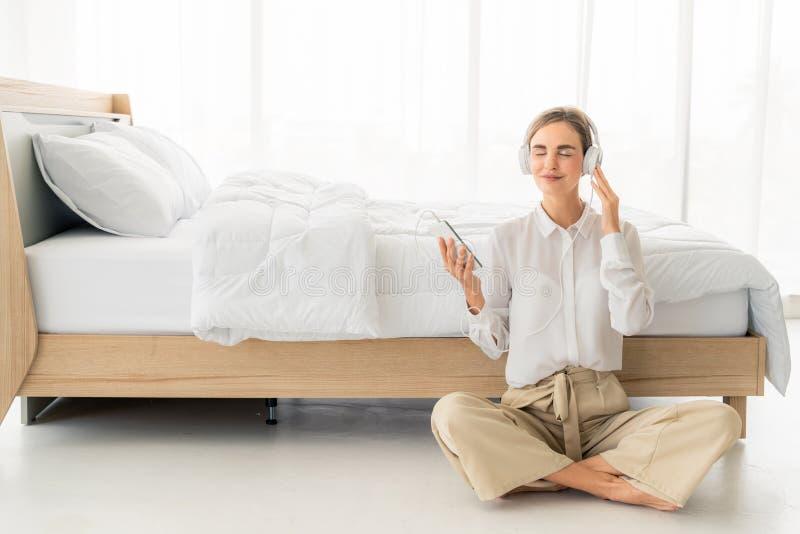 Ευτυχής όμορφη γυναίκα στα ακουστικά που ακούνε τη μουσική και που τραγουδούν καθμένος στο κρεβάτι στοκ εικόνες