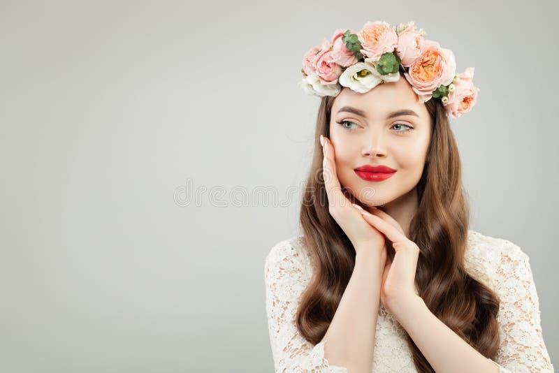 Ευτυχής όμορφη γυναίκα στο γκρίζο υπόβαθρο εμβλημάτων Όμορφο κορίτσι με το σαφές δέρμα, τη μακριά λαμπρά τρίχα και τα λουλούδια στοκ φωτογραφίες με δικαίωμα ελεύθερης χρήσης