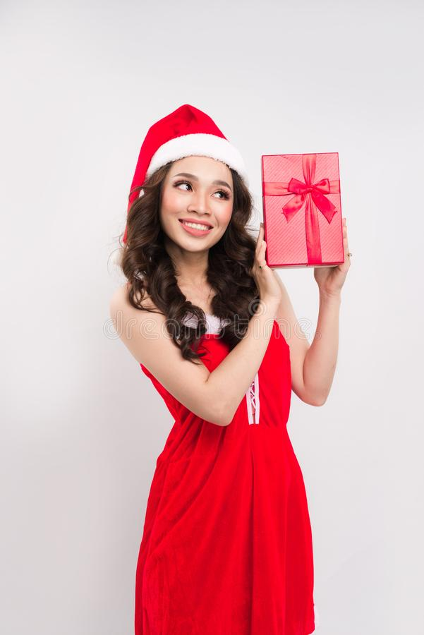 Ευτυχής όμορφη γυναίκα στο κόκκινα φόρεμα και το δώρο εκμετάλλευσης καπέλων Άγιου Βασίλη στοκ φωτογραφίες