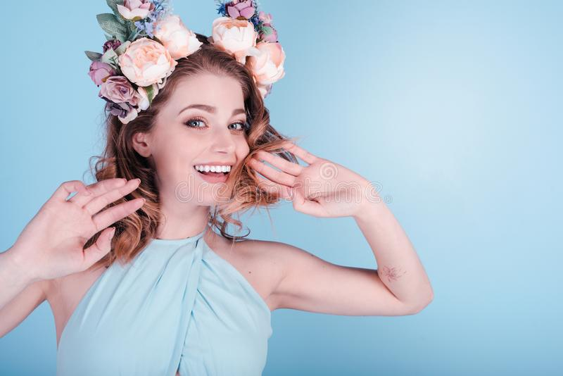 Ευτυχής όμορφη γυναίκα στο στεφάνι λουλουδιών που απομονώνεται στο μπλε υπόβαθρο Συναυλία άνοιξη στοκ εικόνες