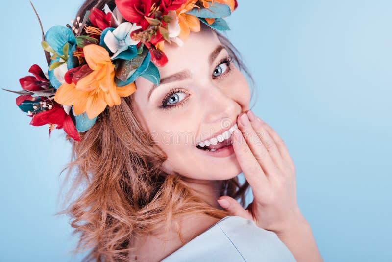 Ευτυχής όμορφη γυναίκα στο στεφάνι λουλουδιών που απομονώνεται στο μπλε υπόβαθρο Συναυλία άνοιξη στοκ φωτογραφία με δικαίωμα ελεύθερης χρήσης