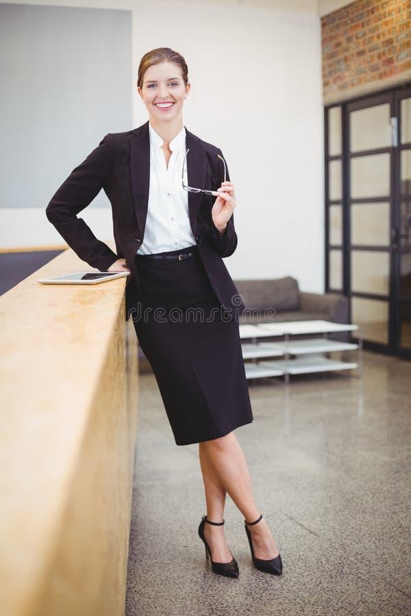 Ευτυχής όμορφη επιχειρηματίας που κλίνει στο μετρητή στην αρχή στοκ εικόνες με δικαίωμα ελεύθερης χρήσης