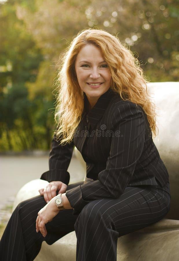 Ευτυχής όμορφη επιχειρησιακή γυναίκα στο πάρκο στοκ φωτογραφία