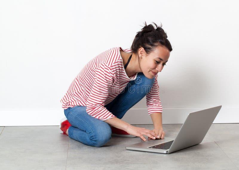 Ευτυχής όμορφη νέα γυναίκα στο πάτωμα, που επικοινωνεί στο PC στοκ εικόνες με δικαίωμα ελεύθερης χρήσης