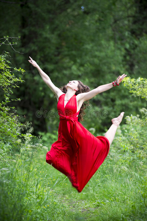 Ευτυχής όμορφη νέα καυκάσια γυναίκα brunette στο κόκκινο φόρεμα που πηδά υπαίθρια στοκ εικόνα με δικαίωμα ελεύθερης χρήσης