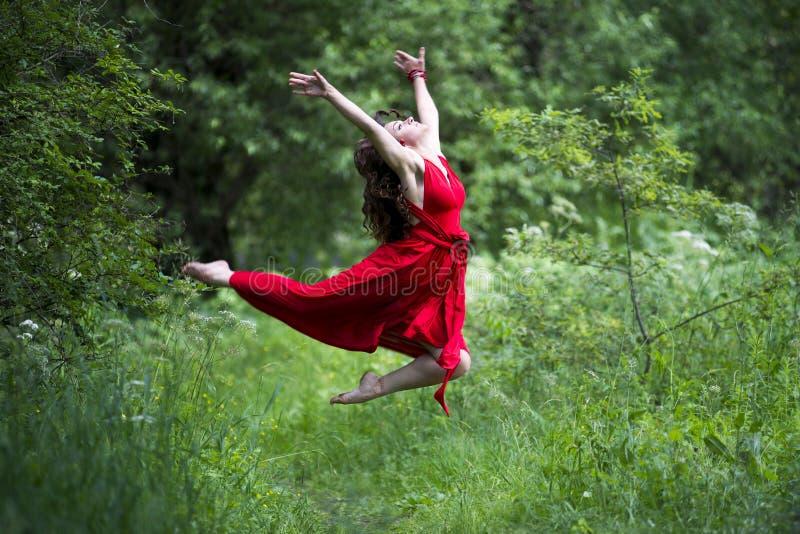 Ευτυχής όμορφη νέα καυκάσια γυναίκα brunette στο κόκκινο φόρεμα που πηδά υπαίθρια στοκ εικόνα