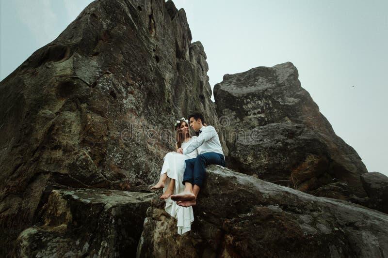 Ευτυχής όμορφη νύφη και κομψός μοντέρνος νεόνυμφος που αγκαλιάζουν στο βράχο στοκ φωτογραφία με δικαίωμα ελεύθερης χρήσης