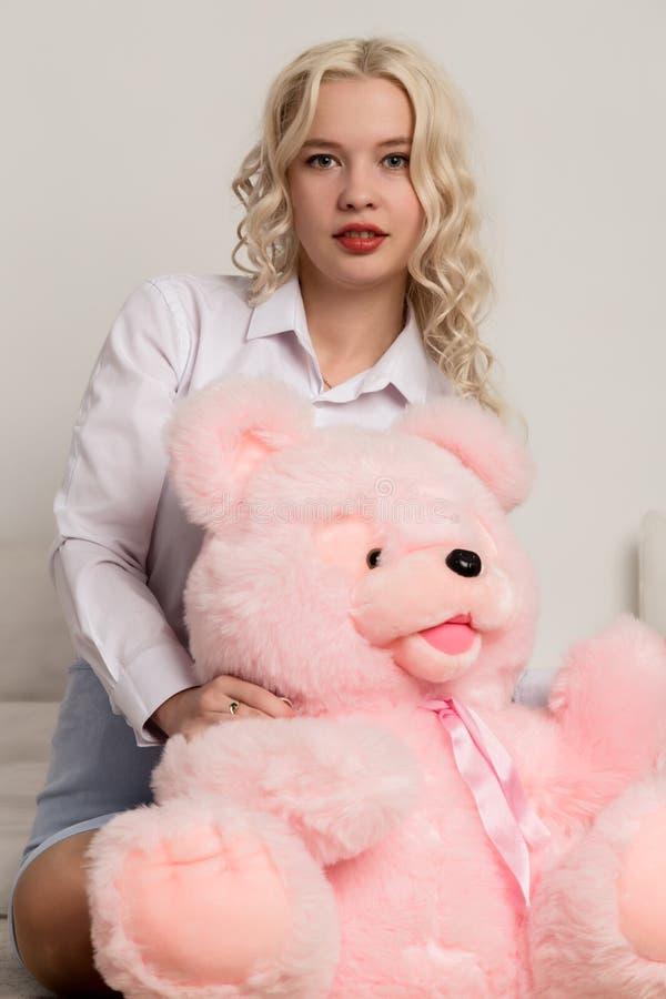 Ευτυχής όμορφη ξανθή γυναίκα που αγκαλιάζει μια teddy αρκούδα Έννοια των διακοπών ή των γενεθλίων στοκ φωτογραφίες