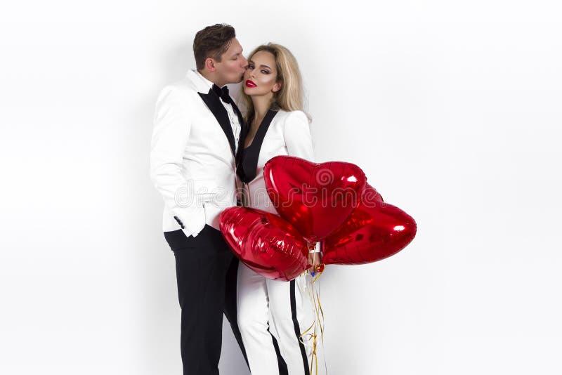 Ευτυχής όμορφη τοποθέτηση ζευγών στο άσπρο υπόβαθρο και κράτημα της καρδιάς μπαλονιών βαλεντίνος ημέρας s στοκ εικόνα με δικαίωμα ελεύθερης χρήσης