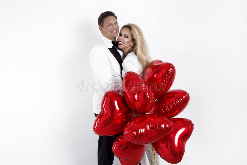 Ευτυχής όμορφη τοποθέτηση ζευγών στο άσπρο υπόβαθρο και κράτημα της καρδιάς μπαλονιών βαλεντίνος ημέρας s στοκ φωτογραφίες