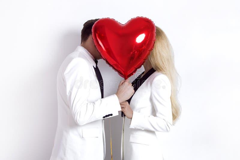 Ευτυχής όμορφη τοποθέτηση ζευγών στο άσπρο υπόβαθρο και κράτημα της καρδιάς μπαλονιών βαλεντίνος ημέρας s στοκ εικόνα