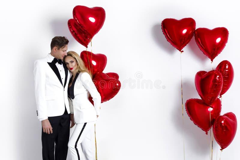 Ευτυχής όμορφη τοποθέτηση ζευγών στο άσπρο υπόβαθρο και κράτημα της καρδιάς μπαλονιών βαλεντίνος ημέρας s στοκ φωτογραφία